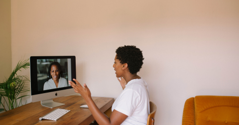 Two women pictured talking through web conference.