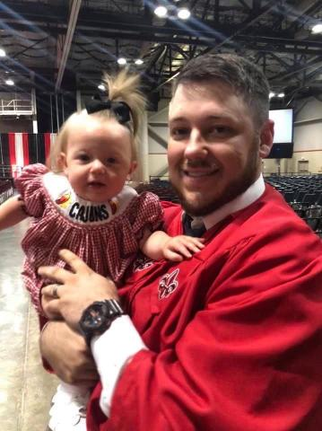 Brian Kidd holds his daughter during his graduation from UL Lafayette.