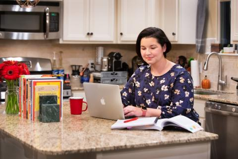 Dani Oldfield works on graduate coursework in her Youngsville kitchen.