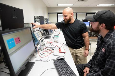 james Guillory works with a student as part of the Master of Science in Systems Technology online program.